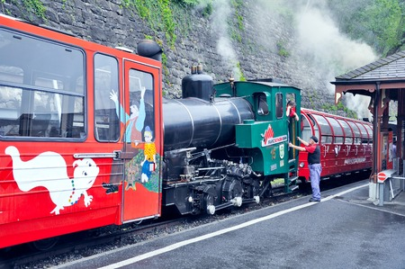 narrow gauge: Brienz, Switzerland - June 12, 2010: Retro train with locomotive crew before departure. Brienz-Rothorn bahn is cogwheel narrow gauge railway with beautiful mountain views. Editorial