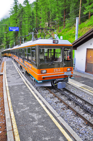 narrow gauge railroads: Zermatt, Switzerland - June 14 2010: Passenger cogwheel train from Gornergrat to Zermatt departs from the platform. Editorial