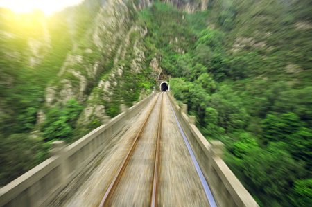 Blurred motion on the railway viaduct toward the tunnel. Spain. Stock Photo