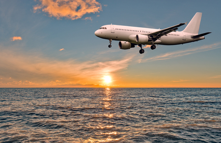 water turbine: Flight of the plane above the ocean before landing at sunset.