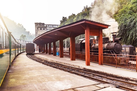 Steam narrow-gauge locomotive and passenger carriages stand by the platforms. Yuejin. Sichuan province. China.