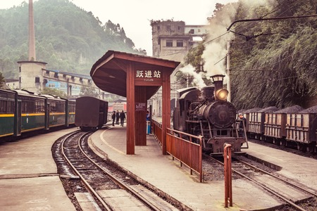 Yuejin, Sichuan province, China, November 03, 2016: Steam narrow-gauge locomotive and passenger carriages stand by the platforms. Editorial