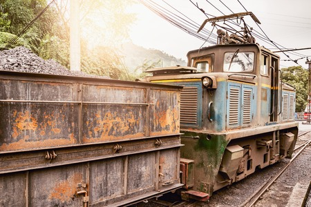 Electric narrow-gauge locomotive stands with the freight train with coal before departure. Yuejin. Sichuan province. China.