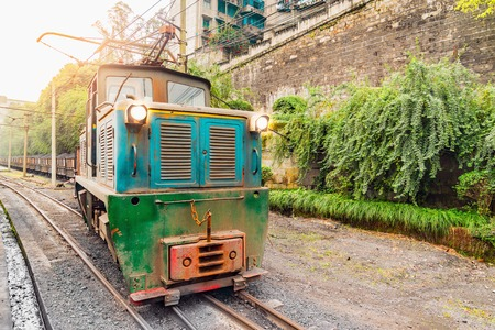 Electric narrow-gauge locomotive stands with the freight train with coal before departure. Yuejin. Jiayang Mining Region. Sichuan province. China. Stock Photo
