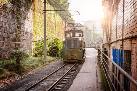 Electric narrow-gauge locomotive with the coal loaded freight train moves through Yuejin town to Shixi. Jiayang Mining Region. Sichuan province. China.