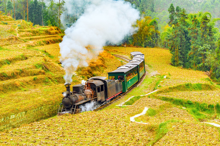 Steam narrow-gauge train moves from Yuejin to Bagou through the chinese countryside. Jiayang Mining Region. Sichuan province. China. Stock Photo