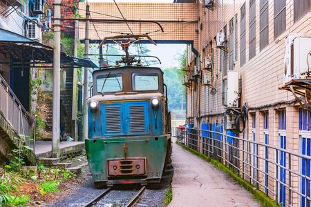 Electric narrow-gauge locomotive with the empty freight train moves through Yuejin town. Jiayang Mining Region. Sichuan province. China