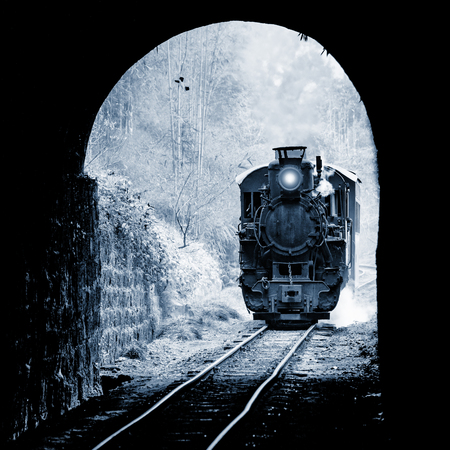 Steam narrow-gauge train from Yuejin to Bagou approaches to the tunnel. Jiayang Mining Region. Sichuan province. China. Vintage style image.