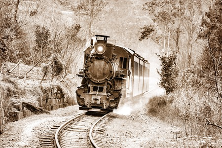 Steam narrow-gauge train moves from Bagou to Yuejin through the jungle. Jiayang Mining Region. Sichuan province. China. Vintage style image. Stock Photo