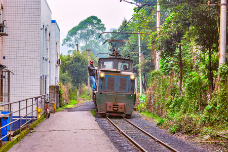 Yuejin, Jiayang Mining Region, Sichuan province, China, November 05, 2016: Electric narrow-gauge locomotive with the freight train moves through Yuejin town. Editorial
