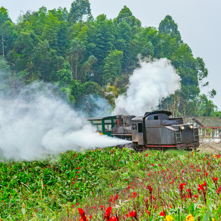 Steam narrow-gauge train with local people moves from Bagou to Yuejin. Jiayang Mining Region. Sichuan province. China.