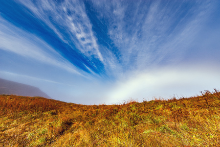 withering: Fantastic cloudscape and rainbow above the mountain meadow at autumn morning time. Caucasus. Russia.