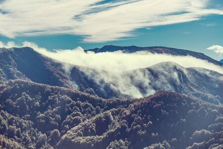 withering: Clouds above the mountains at autumn day time. Caucasus. Russia.