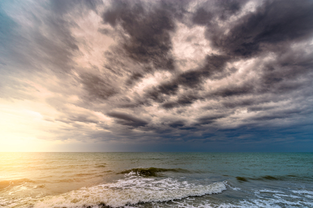 Dark stormy sky and sunlight above the ocean surface Stock Photo