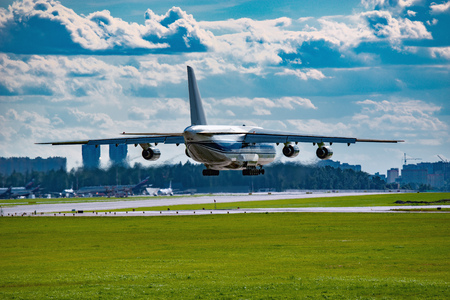 Landing of the big cargo airliner at sunny day time.