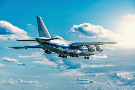 Flight of the big cargo airliner at sunny day time. Stock Photo