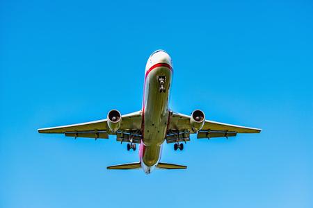 Flight of the passenger plane at sunset time. Stock Photo