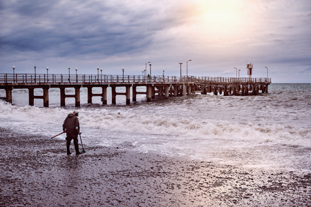 Gold seeker on the sea coast at stormy evening time. Stock Photo