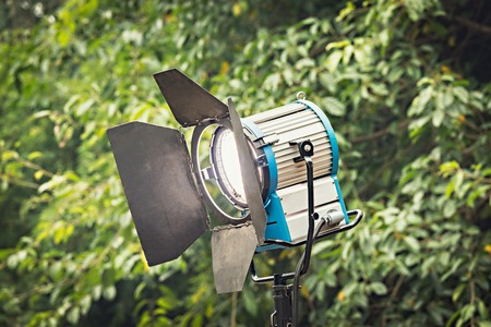 Spotlight on green trees background. Lighting equipment for studio photography or videography.