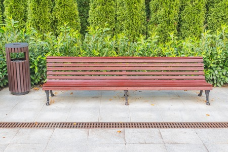 Wooden bench and bin for waste in the city park. Stock Photo