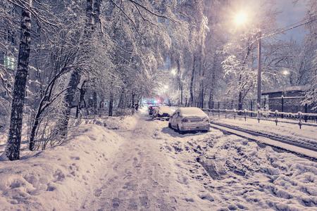 Cars under the snow on the night winter city street.