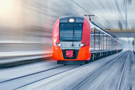 Modern high-speed train moves fast at winter evening time.