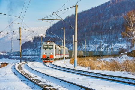 Freight train moves along Baikal lake. Trans Siberian railway. Russia.