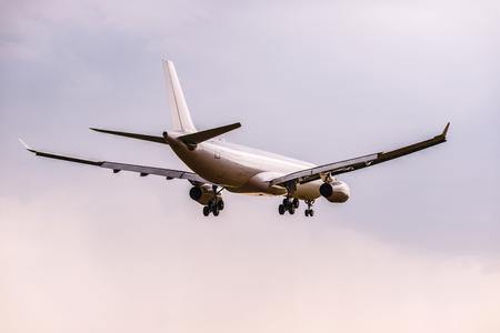 Landing van het passagiersvliegtuig bij zonsondergang. Stockfoto - 101073824