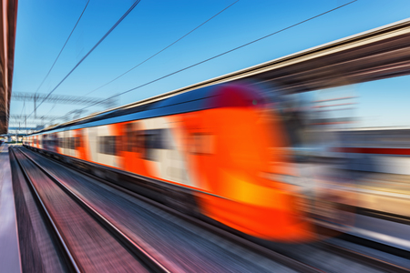 Modern high-speed train moves fast along the platform. Blurred image.