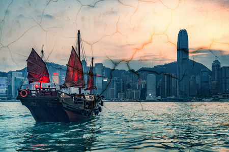 Retro small ship in Hong Kong harbour at sunset time. Vintage style image.