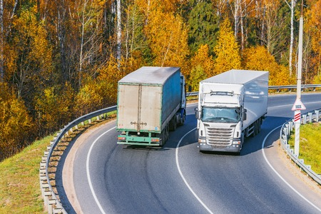 Freight trucks move on the road at autumn day time.