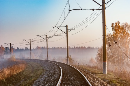 Electric railway line at autumn early morning time. Stock Photo