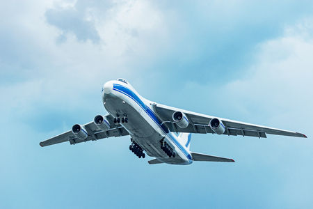 Flight of the big cargo airliner at cloudy day time. Stock Photo