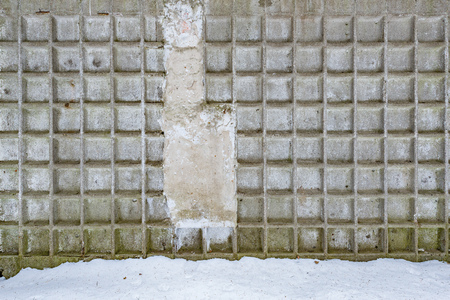 Gray background of the cement wall texture by the snow on the ground.