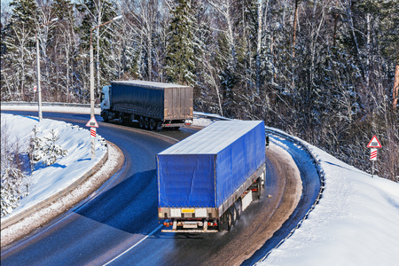 Freight trucks move on the road at winter day time. Stock Photo