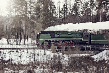 Steam train moves forward at cold winter morning time. 免版税图像