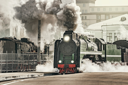 Steam train departs from the railway station. Imagens