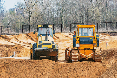 Bulldozer and road roller stand on the construction site.