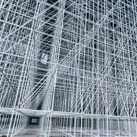 Vertical scaffolding formed a myriad of grid. Industrial and modern urban construction background.