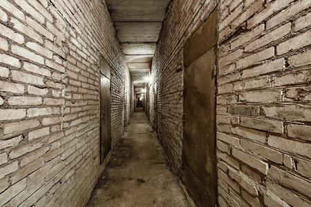 Dark narrow corridor of the basement. Stock Photo