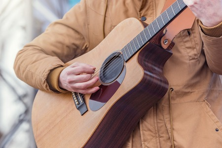 Mans hands playing acoustic guitar on the stage.