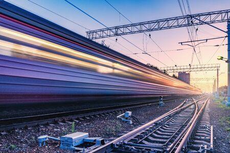 Pociąg pasażerski porusza się szybko w czasie zachodu słońca.