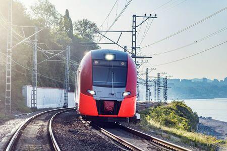 Modern high-speed train moves along the Black sea coast. Sochi. Russia.