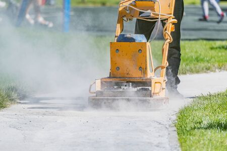 Worker making with special machine narrow road in the city park.
