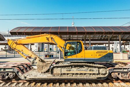 Excavator stands on the railway transporter by the platform.