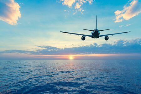 Vliegen van het passagiersvliegtuig boven het zeeoppervlak bij zonsondergang. Stockfoto