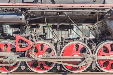 Wheels of the retro steam train standing by the platform. Imagens