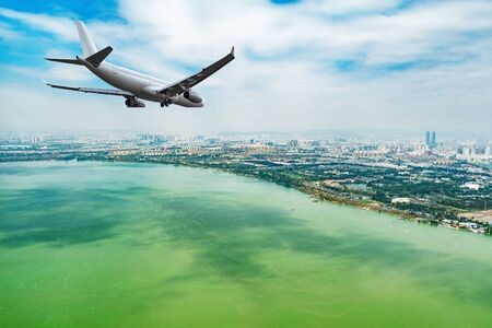 Flight of the passenger plane above the lake by the city.