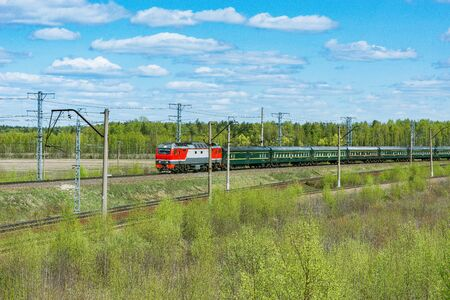 Passenger train from Beijing to Moscow approaches to the station at spring day time.