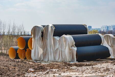 Stacked corrugated pieces of tubes on the construction site.